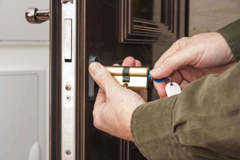 Locksmith repairing the lock on a house door