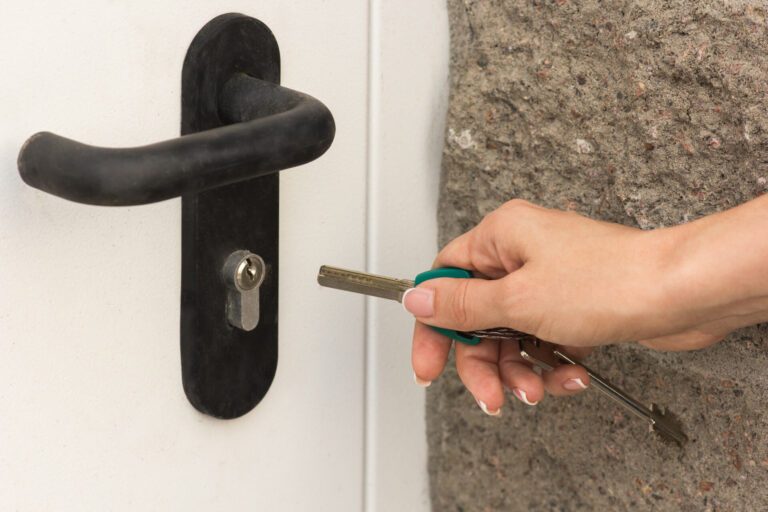 girl-opens-front-door-with-key-close-up