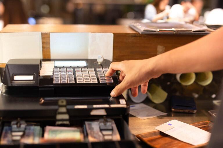 hand-pressing-electronic-cash-register-shop